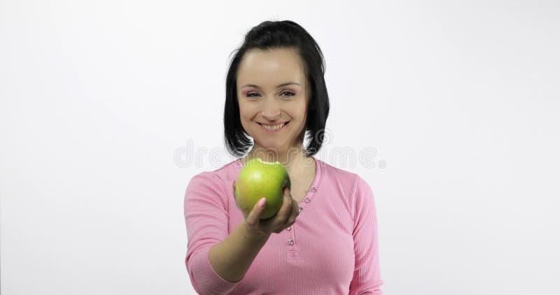 Νέος όμορφος με το πράσινο δάγκωμα προσφοράς μήλων στο θεατή ( στοκ εικόνες