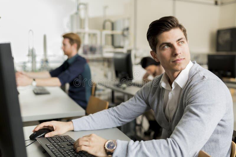 Νέος όμορφος σπουδαστής που χρησιμοποιεί τον υπολογιστή στοκ φωτογραφία με δικαίωμα ελεύθερης χρήσης