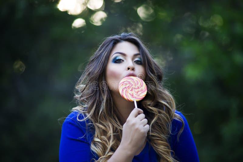 Νέος όμορφος συν το πρότυπο μεγέθους στο μπλε φόρεμα υπαίθρια, xxl γυναίκα στη φύση που γλείφει ένα lollipop στοκ φωτογραφία