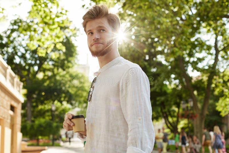 Νέος όμορφος τύπος με την τρίχα πιπεροριζών και γενειάδα στον άσπρο καφέ κατανάλωσης πουκάμισων και αναμονή της φίλης του μια ημε στοκ φωτογραφία με δικαίωμα ελεύθερης χρήσης