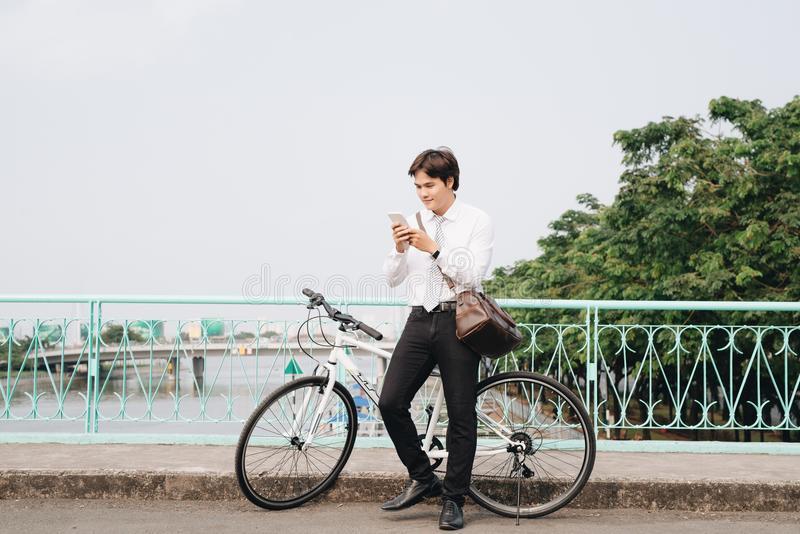 Νέος όμορφος τύπος σε ένα ποδήλατο που εξετάζει το κινητό τηλέφωνο στοκ φωτογραφία με δικαίωμα ελεύθερης χρήσης