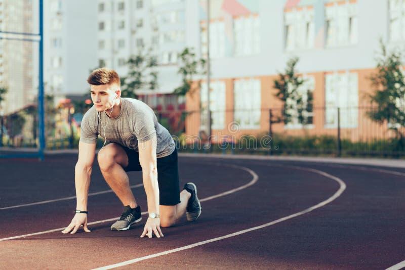 Νέος όμορφος τύπος στον αθλητισμό το πρωί στο στάδιο Φορά τα αθλητικά ενδύματα, ακούοντας τη μουσική μέσω των ακουστικών Αυτός στοκ εικόνες