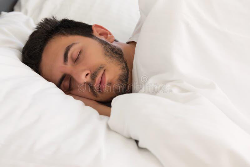 Νέος όμορφος ύπνος ατόμων στο κρεβάτι του στοκ εικόνα