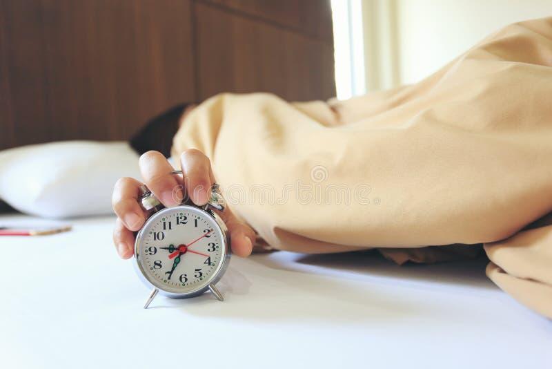 Νέος ύπνος γυναικών στην κρεβατοκάμαρα με τη λαβή το ξυπνητήρι το πρωί, έννοια υγείας στοκ εικόνες
