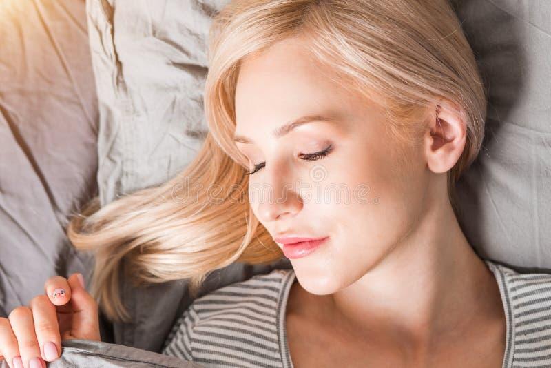 Νέος ύπνος γυναικών στο κρεβάτι στοκ φωτογραφία με δικαίωμα ελεύθερης χρήσης