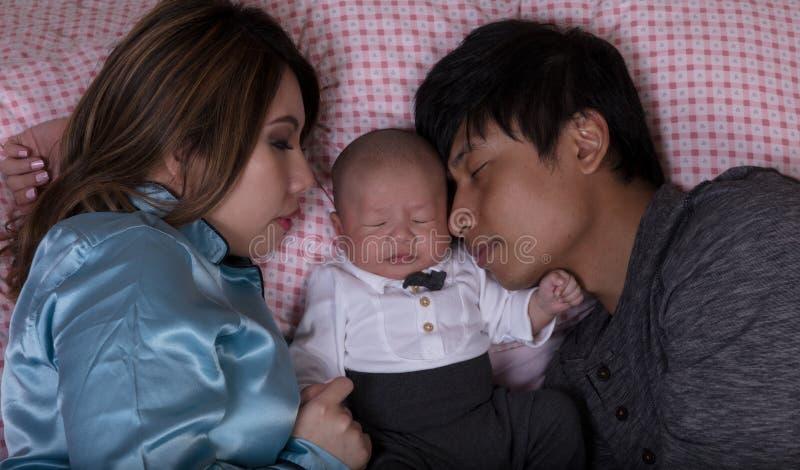 Νέος ύπνος ζευγών με το μωρό νηπίων στο κρεβάτι στοκ φωτογραφία με δικαίωμα ελεύθερης χρήσης