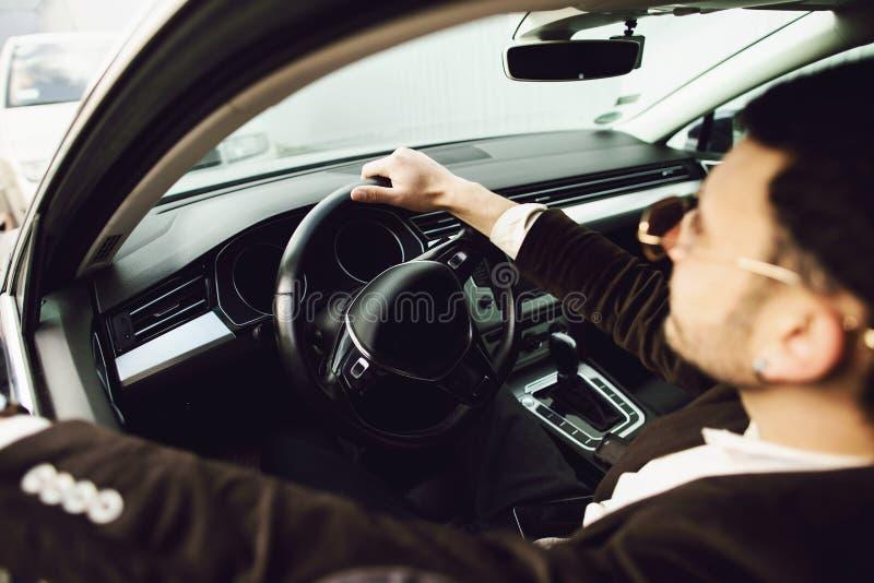 Νέος bussinesman στο κοστούμι και τα μαύρα γυαλιά που οδηγούν το αυτοκίνητό του Η επιχείρηση κοιτάζει Τεστ δοκιμής του νέου αυτοκ στοκ εικόνα με δικαίωμα ελεύθερης χρήσης