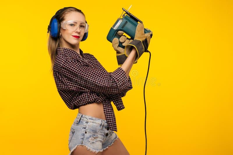 Νέος craftswoman με ένα τορνευτικό πριόνι μπροστά από το κίτρινο υπόβαθρο στοκ εικόνα με δικαίωμα ελεύθερης χρήσης