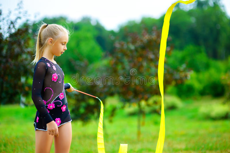 Νέος gymnast θερμαίνει με μια γυμναστική ταινία ή στοκ εικόνες