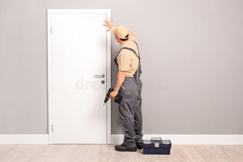 Νέος handyman εγκαθιστώντας μια πόρτα στοκ εικόνα με δικαίωμα ελεύθερης χρήσης
