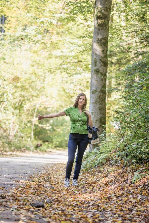 Νέος hitchhiker γυναικών που στέκεται στο δάσος φθινοπώρου στοκ φωτογραφία με δικαίωμα ελεύθερης χρήσης
