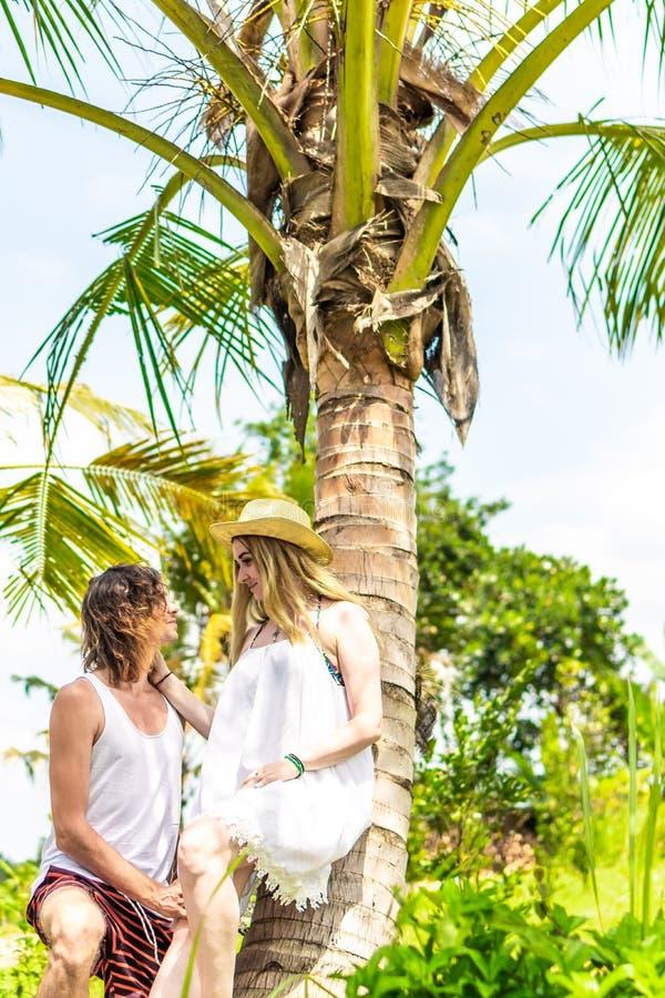Νέος romatic τουρίστας ζευγών κάτω από το φοίνικα καρύδων Βεραμάν και κίτρινη εικόνα Νησί του Μπαλί Ινδονησία στοκ φωτογραφίες
