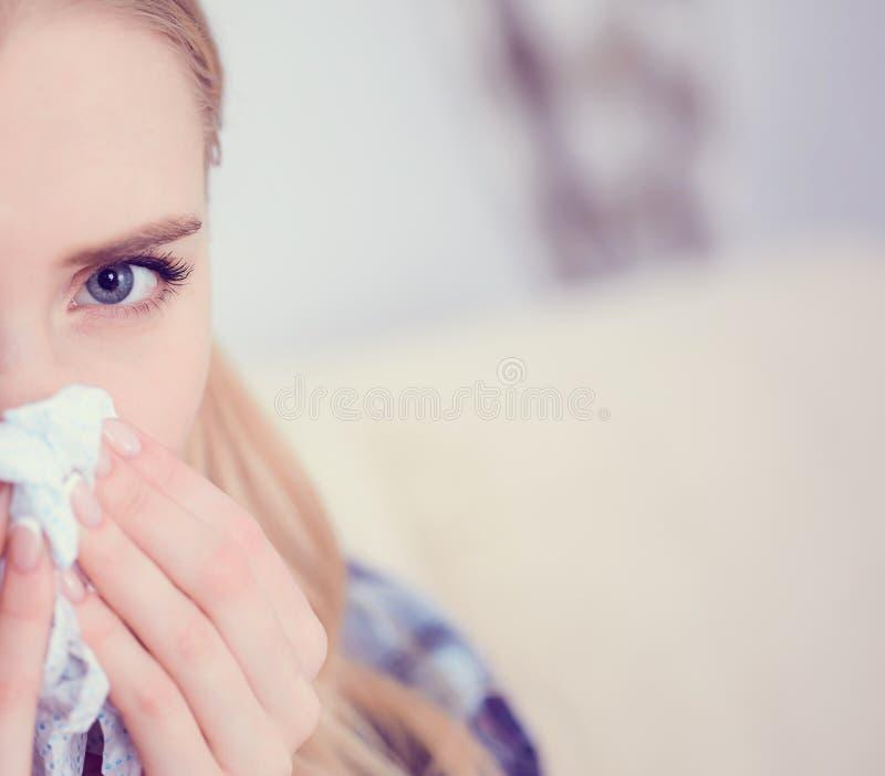 Νέο άρρωστο καυκάσιο sneeze γυναικών στο σπίτι στον καναπέ με ένα κρύο Χρησιμοποιημένο κορίτσι έγγραφο ιστού που φυσά τη μύτη της στοκ εικόνες με δικαίωμα ελεύθερης χρήσης