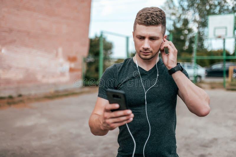 Νέο άτομο αθλητών τύπων, σοβαρή οθόνη βλέμματος του smartphone, που μιλά στην τηλεοπτική κλήση Καλοκαίρι στο πάρκο πόλεων στο υπό στοκ φωτογραφίες