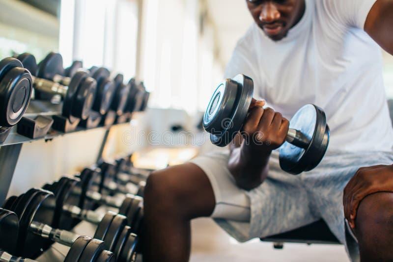 Νέο άτομο αφροαμερικάνων που κάθεται και που ανυψώνει έναν αλτήρα με το ράφι στη γυμναστική στοκ εικόνα