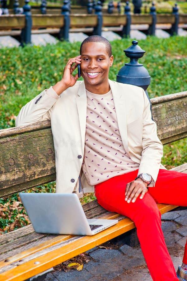 Νέο άτομο αφροαμερικάνων που μιλά στο τηλέφωνο κυττάρων, που λειτουργεί στην περιτύλιξη στοκ εικόνα