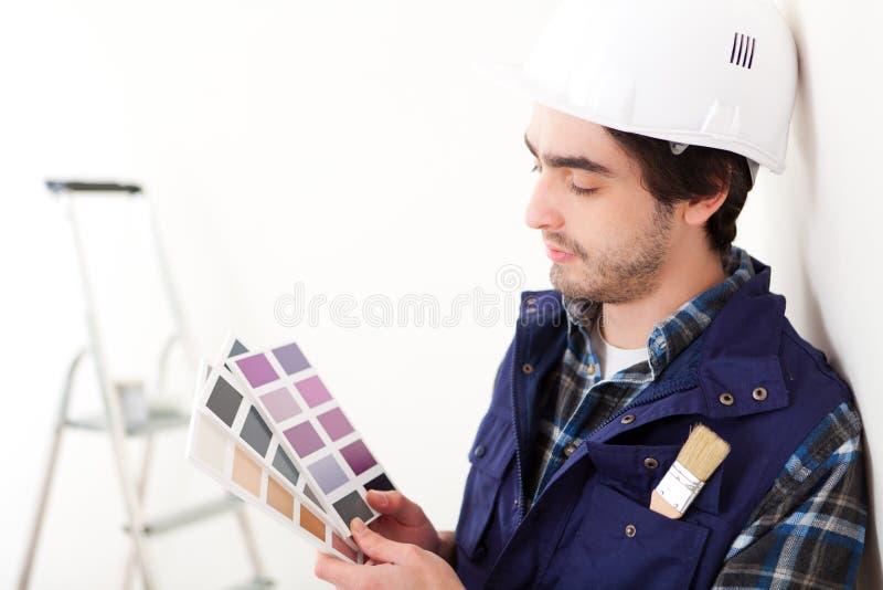 Νέο άτομο εργαζομένων που επιλέγει το χρώμα του επιπέδου του στοκ φωτογραφίες
