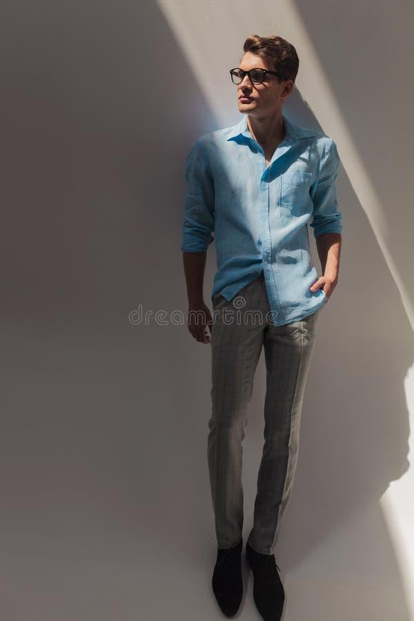 Νέο άτομο μόδας που κλίνει σε έναν γκρίζο τοίχο στοκ εικόνες