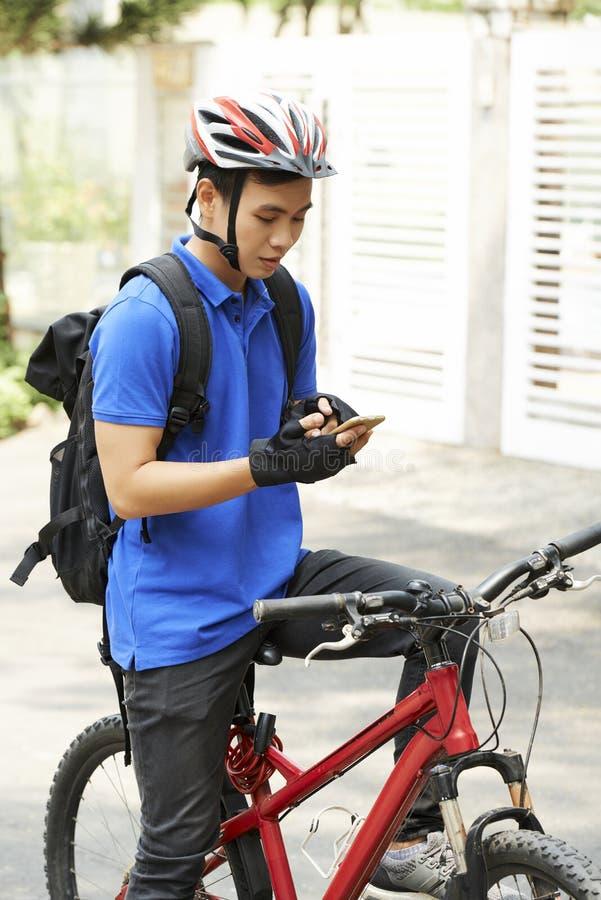 Νέο άτομο παράδοσης που ελέγχει την εφαρμογή στο τηλέφωνό του στοκ εικόνα με δικαίωμα ελεύθερης χρήσης