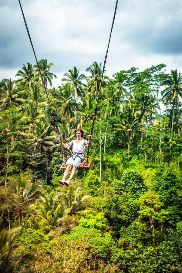 Νέο άτομο τουριστών με τη μακρυμάλλη ταλάντευση στον απότομο βράχο στο τροπικό δάσος ζουγκλών ενός τροπικού νησιού του Μπαλί στοκ εικόνες με δικαίωμα ελεύθερης χρήσης