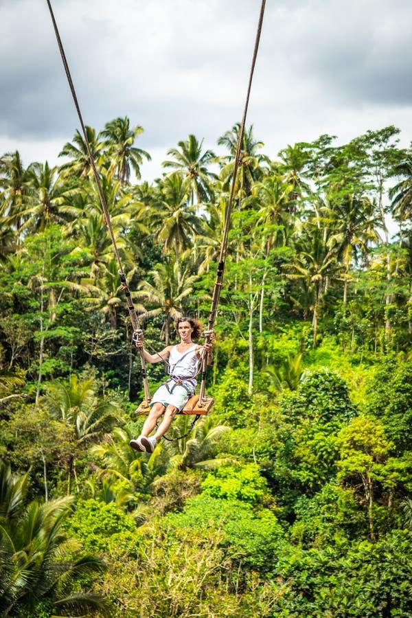 Νέο άτομο τουριστών με τη μακρυμάλλη ταλάντευση στον απότομο βράχο στο τροπικό δάσος ζουγκλών ενός τροπικού νησιού του Μπαλί στοκ φωτογραφίες