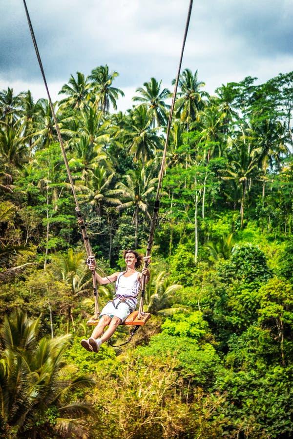 Νέο άτομο τουριστών με τη μακρυμάλλη ταλάντευση στον απότομο βράχο στο τροπικό δάσος ζουγκλών ενός τροπικού νησιού του Μπαλί στοκ εικόνες