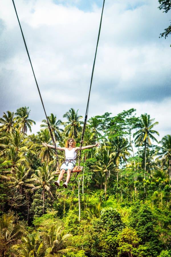 Νέο άτομο τουριστών με τη μακρυμάλλη ταλάντευση στον απότομο βράχο στο τροπικό δάσος ζουγκλών ενός τροπικού νησιού του Μπαλί στοκ εικόνα με δικαίωμα ελεύθερης χρήσης