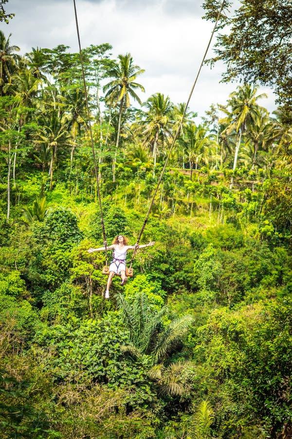 Νέο άτομο τουριστών με τη μακρυμάλλη ταλάντευση στον απότομο βράχο στο τροπικό δάσος ζουγκλών ενός τροπικού νησιού του Μπαλί στοκ φωτογραφία με δικαίωμα ελεύθερης χρήσης