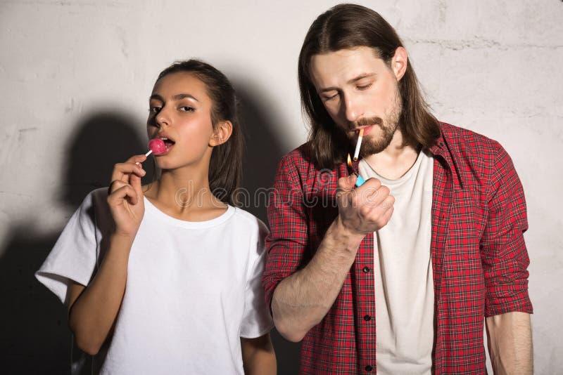 Νέο άτομο hipster με το τσιγάρο κοντά στη φίλη που τρώει την καραμέλα στοκ εικόνες με δικαίωμα ελεύθερης χρήσης