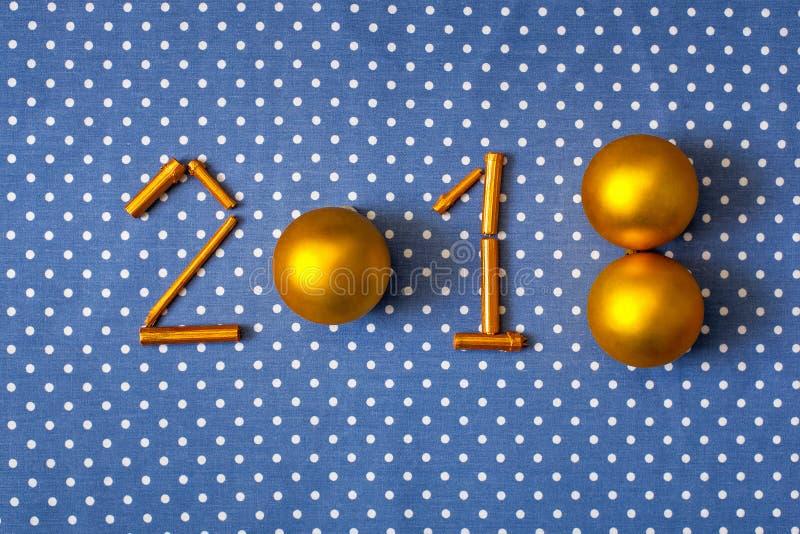 Νέο έτος 2018 αριθμών χρυσές σφαίρες Χριστουγέννων και επιχρυσωμένα ραβδιά σε ένα υπόβαθρο υφασμάτων στα σημεία Πόλκα στοκ φωτογραφίες με δικαίωμα ελεύθερης χρήσης