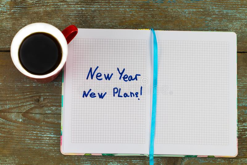 ` Νέο έτος, νέο κείμενο σχεδίων ` στο σημειωματάριο, με το φλιτζάνι του καφέ και τη μάνδρα στον ξύλινο πίνακα - έννοια επιχειρήσε στοκ εικόνες