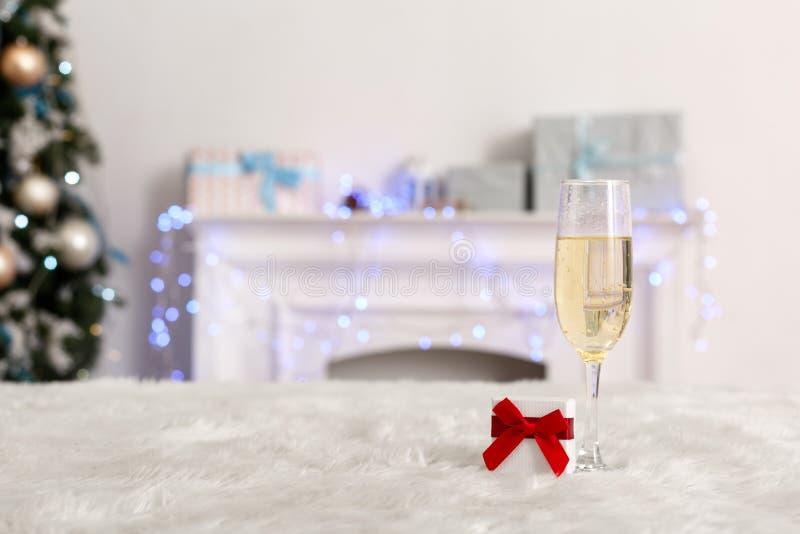 νέο έτος Το διακοσμημένο δωμάτιο κανένα ποτήρι ανθρώπων της σαμπάνιας και του μικρού δώρου στην επιτραπέζια κινηματογράφηση σε πρ στοκ φωτογραφία με δικαίωμα ελεύθερης χρήσης