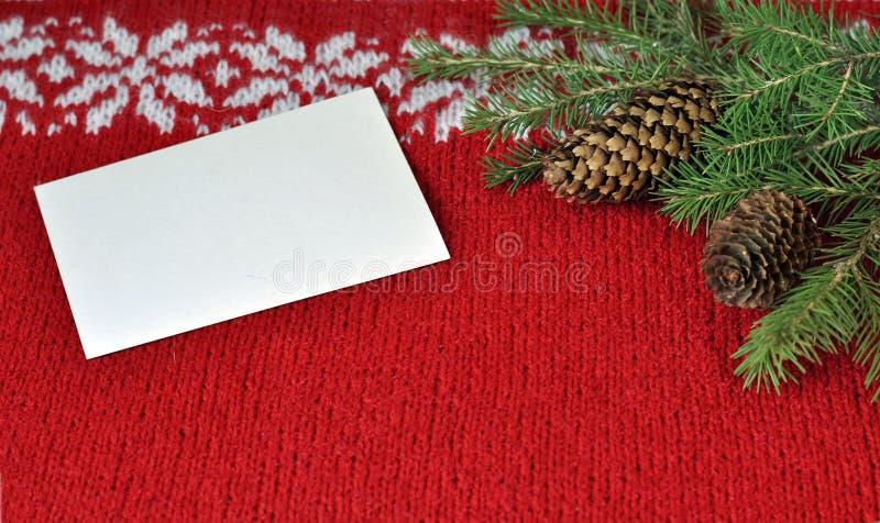 νέο έτος Χριστουγέννων Κομψοί κλάδοι και άσπρη κάρτα στο κόκκινο με το άσπρο πλέκοντας υπόβαθρο διακοσμήσεων στοκ φωτογραφίες με δικαίωμα ελεύθερης χρήσης