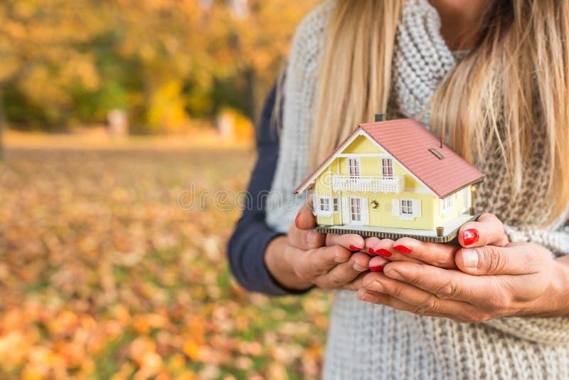 Νέο αγαπώντας ζεύγος που κρατά το μικρό πρότυπο σπίτι στοκ φωτογραφίες
