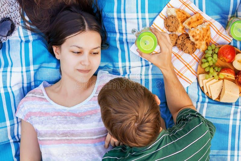 Νέο αγαπώντας ζεύγος που στηρίζεται σε ένα πικ-νίκ μια θερινή ημέρα στοκ εικόνα