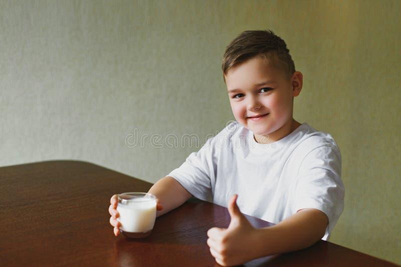 Νέο αγόρι, γάλα, πρωί στην κουζίνα στοκ εικόνα