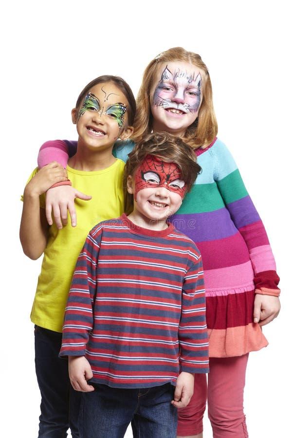 Νέο αγόρι και δύο κορίτσια με τη ζωγραφική προσώπου της γάτας, πεταλούδα και στοκ εικόνες