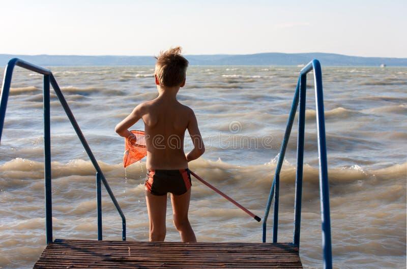 Νέο αγόρι με την προσγείωση καθαρή στην παραλία στοκ εικόνα