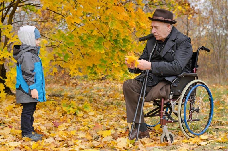 Νέο αγόρι με τον ανάπηρο παππού του στοκ φωτογραφίες