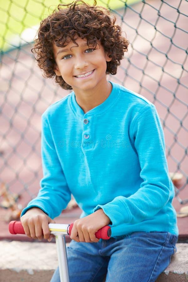 Νέο αγόρι με το μηχανικό δίκυκλο στο πάρκο στοκ φωτογραφία με δικαίωμα ελεύθερης χρήσης