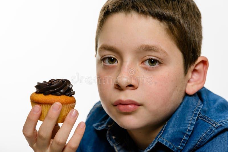 Νέο αγόρι με το πουκάμισο τζιν που τρώει τη σοκολάτα cupcake, απομονωμένο στο λευκό υπόβαθρο στενό πορτρέτο επάνω στοκ φωτογραφία με δικαίωμα ελεύθερης χρήσης
