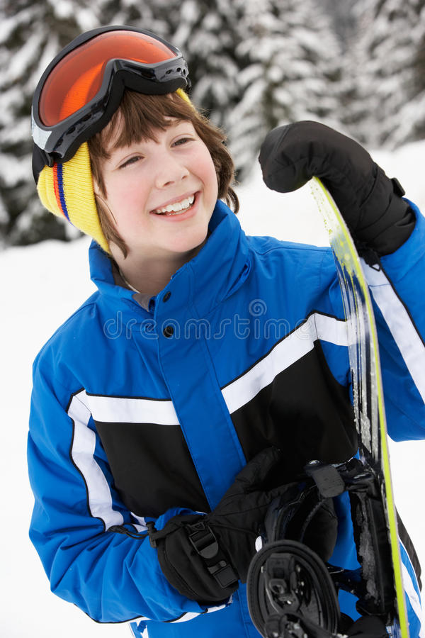 Νέο αγόρι με το σνόουμπορντ στις διακοπές σκι στοκ φωτογραφία