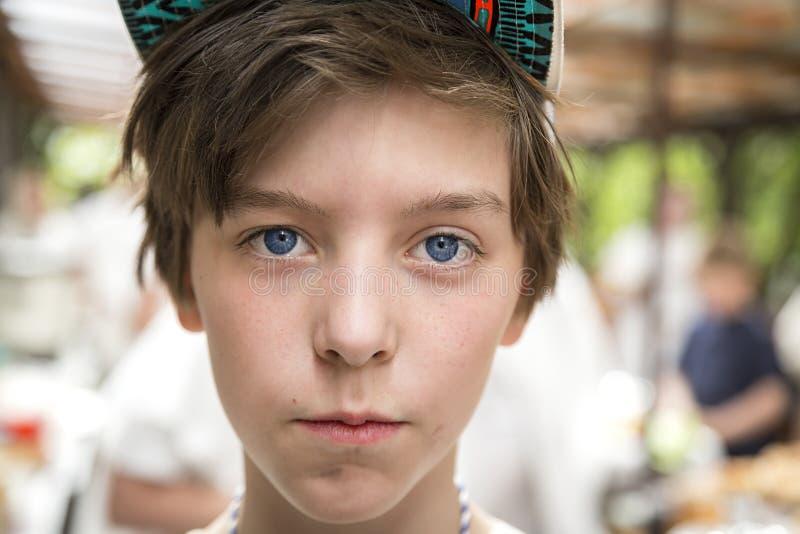 Νέο αγόρι με το basecap που εξετάζει τη κάμερα στοκ φωτογραφία
