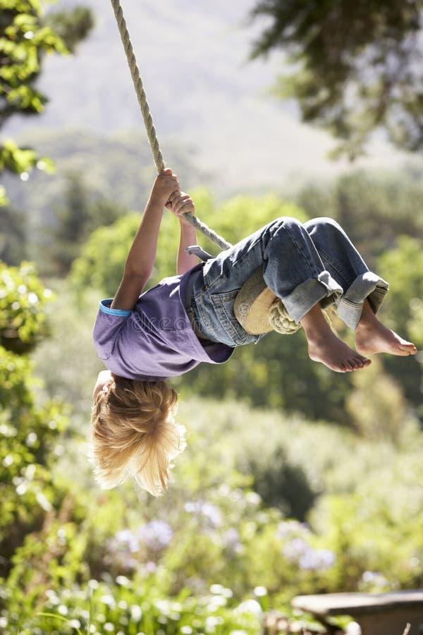 Νέο αγόρι που έχει τη διασκέδαση στην ταλάντευση σχοινιών στοκ φωτογραφία