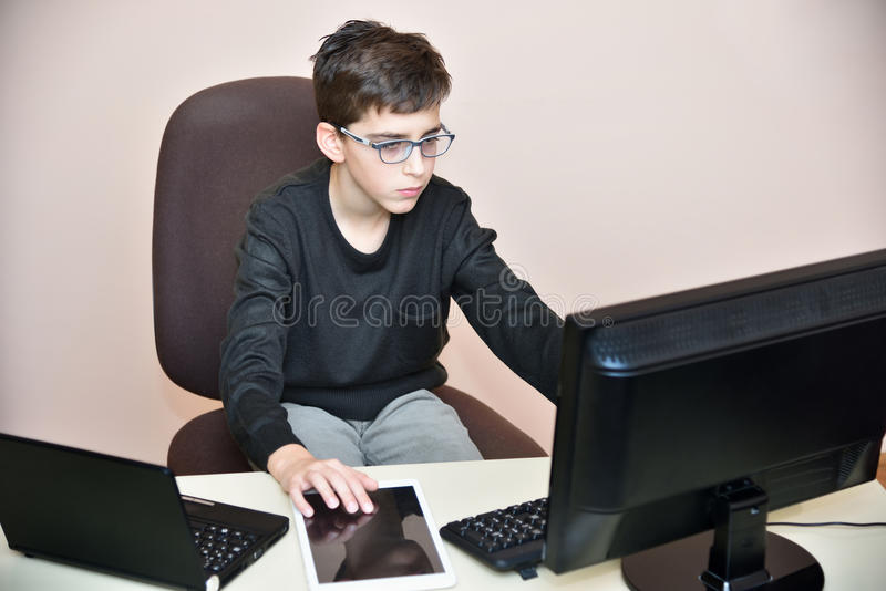 Νέο αγόρι που εργάζεται στους υπολογιστές στοκ εικόνες
