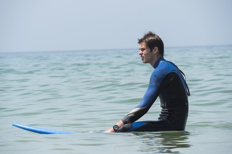 Νέο αγόρι που κάνει σερφ στη θάλασσα, περιμένοντας κύματα στοκ εικόνες με δικαίωμα ελεύθερης χρήσης