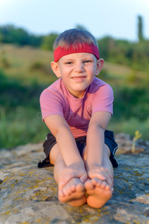 Νέο αγόρι που κάνει τις τεντώνοντας ασκήσεις στοκ φωτογραφία με δικαίωμα ελεύθερης χρήσης