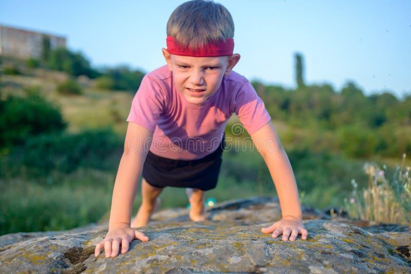 Νέο αγόρι που κάνει το ώθηση-UPS σε έναν βράχο στοκ εικόνα με δικαίωμα ελεύθερης χρήσης