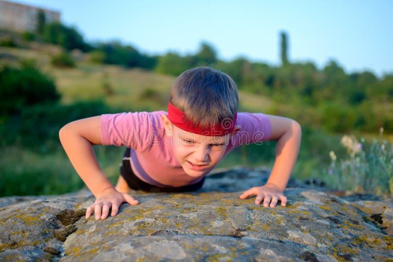 Νέο αγόρι που κάνει το ώθηση-UPS σε έναν βράχο στοκ εικόνες