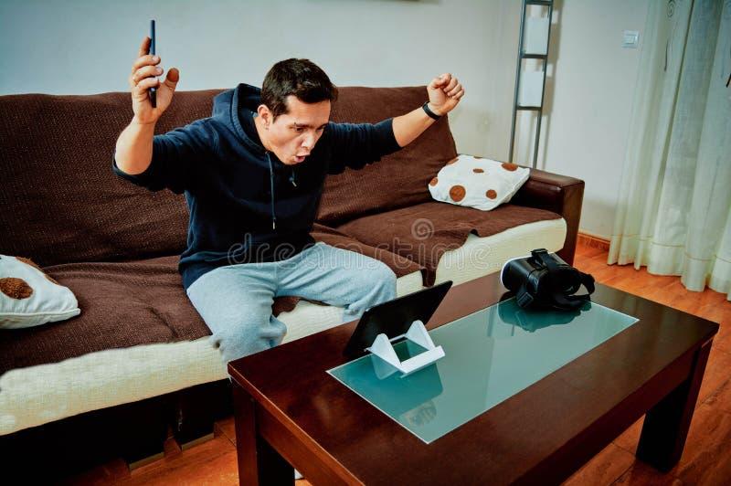 Νέο αγόρι που κερδίζει τα τηλεοπτικά παιχνίδια στην ταμπλέτα του στοκ φωτογραφία με δικαίωμα ελεύθερης χρήσης